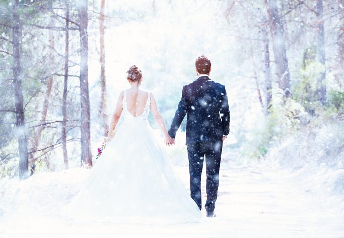 Winter Weddings - Couple in a pine forest while snowing